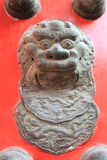 Chinese bronze lion on the red gate Stock Photo