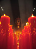Chinese buddha in the smoke with red candles Stock Photos