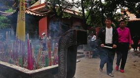 Panning shot in Chinese Buddhist temple with people. Chinese Buddhist temple in Kunming. Although Chinese society is predominantly atheist, the number of stock video footage