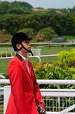 Chinese bugler in jockey gear begins Emirates Singapore Derby at Kranji Turf Club horse race Royalty Free Stock Image