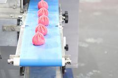 Chinese buns in food production conveyor. Red stock images