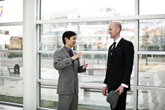 Chinese Business explaining details. A Chinese Business men explaining details to a European colleague. Two satisfied businessmen Stock Photos