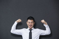 Chinese business man flexing his arms. Stock Photos