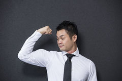 Chinese business man flexing his large bicep. Stock Photography