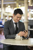 Chinese business man in a food court using his phone. Royalty Free Stock Photo
