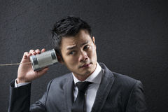 Chinese Business man Listening to a Tin Can Phone. Royalty Free Stock Photos