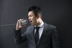 Chinese Business man shouting into a Tin Can Phone. Royalty Free Stock Images