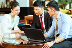 Chinese business people at meeting in hotel lobby Royalty Free Stock Images