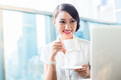 Chinese Business woman drinking coffee having break Royalty Free Stock Photography