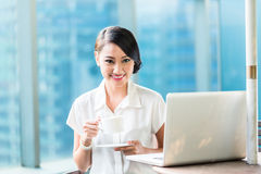 Chinese Business woman drinking coffee having break Stock Photo