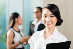 Chinese Business woman in front of team Stock Photo