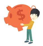 Chinese businessman carries a big piggy bank for Royalty Free Stock Photo