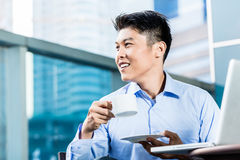 Chinese Businessman with coffee, laptop, and skyline Stock Photo