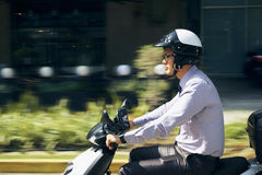 Chinese Businessman Commuter Riding Scooter Motorcycle In City Royalty Free Stock Images