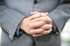 A Chinese Businessman folded hands,. A close-up of the folded hands of a Chinese Businessman who is thinking about a proposition Royalty Free Stock Photo