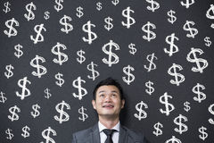 Chinese businessman in front of dollar signs written on wall. Stock Image