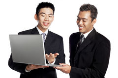 Chinese businessman with Malay colleague. Business exchange using laptop between two asian businessmen. Racial harmony. Studio shot isolated on white Stock Photography