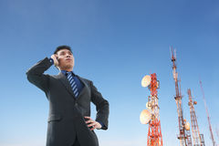 Chinese businessman on phone and antenna Royalty Free Stock Photo