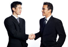 Chinese businessman shaking hands with African. A Chinese, asian businessman shaking hands and smiling with an African business associate. Signifies the closing Stock Image