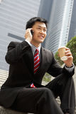 Chinese Businessman Talking On Mobile Phone. With Takeaway Coffee Royalty Free Stock Images