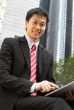 Chinese Businessman Working On Tablet Computer. Outside Office Smiling Stock Photo