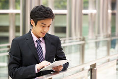 Chinese Businessman Working On Tablet Computer. Outside Office Stock Photo