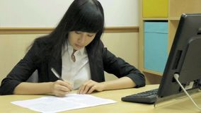 Chinese businesswoman at desk writing stock footage