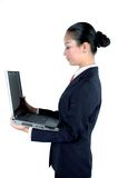 Chinese businesswoman with laptop. Chinese businesswoman busy with work, holding laptop, wearing elegant suit Royalty Free Stock Image