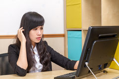 Chinese Businesswoman sitting at desk, confused royalty free stock image