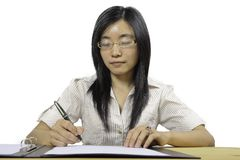 Chinese businesswoman, sitting at desk writing Royalty Free Stock Photography