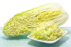 Chinese cabbage. Is heading out on a glass surface. Chopped cabbage is on the front of the saucer Stock Images