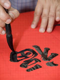 Chinese Calligrapher. Man writing Chinese calligraphy on red paper Royalty Free Stock Images