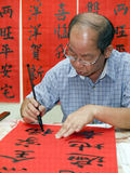 Chinese Calligrapher. Man writing Chinese calligraphy on red paper Stock Images