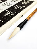 Chinese calligraphy art. An image of a chinese calligraphic brush beside a book for learning about calligraphy. Open page of book shows standard way of how to stock images