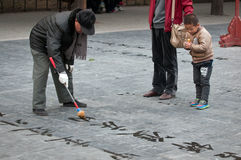 Chinese calligraphy. Beijing, China - March 26th, 2013: Kid looking on Chinese letters written by old man practising calligraphy in Temple of Heaven park area royalty free stock photo