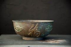 Chinese Calligraphy Copper Dragon Bowl. Rustic copper metal bowl with Chinese calligraphy and dragon symbols. Empty bowl meditation stock image