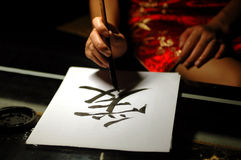 Chinese calligraphy, love sign. Chinese handwriting, art of calligraphy. Sign Ai - means LOVE. Written by femal in traditional Chinese dress Stock Photography