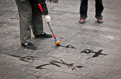 Chinese calligraphy. Man practising chinese calligraphy near the Temple of Heaven in Beijing, China royalty free stock image