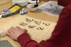 Chinese calligraphy. Student making calligraphy exercise on sheet Stock Image