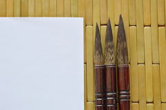 Chinese calligraphy variety size and white paper on bamboo Stock Image