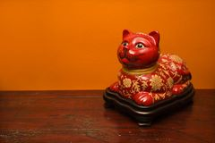 Chinese cat statue. Chinese red cat statue against orange wall royalty free stock photos