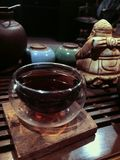 The tea ceremony, dark small glass cup of tea royalty free stock photography