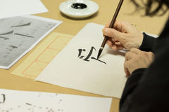 Chinese character calligraphy. Hand holding wooden paint brush over sheet with Chinese character calligraphy on tabletop royalty free stock images
