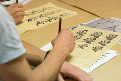 Chinese character calligraphy. Hand holding wooden paint brush over sheet with Chinese character calligraphy on tabletop stock photo