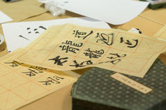 Chinese character calligraphy. Sheets with Chinese character calligraphy on tabletop stock images
