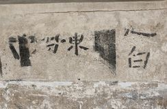 Chinese characters on plaster wall stock image