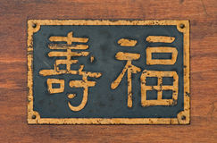 Chinese characters for Happiness & Long Life sign. This is a metal sign found on an antique wood mah-jong game box. The Chinese characters read in English: long Stock Photo