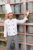 Chinese chef showing dishes. Young male smiling Chinese cook or chef in white uniform with hat showing stock of dishes arranged in closets in a large hotel Royalty Free Stock Photo