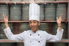 Chinese chef showing dishes. Young male smiling Chinese cook or chef in white uniform with hat showing stock of dishes arranged in closets in a large hotel Stock Photo