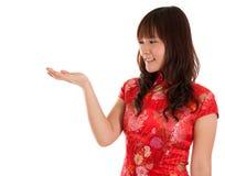 Chinese Cheongsam-Frau, die etwas zeigt Lizenzfreie Stockfotografie